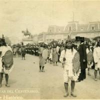 """Fig. 20. """"Guerrieri aztechi"""" alla parata per il centenario dell'Indipendenza lungo il Paseo de la Reforma. Si osservi, sullo sfondo, la statua equestre di Carlo IV."""